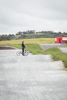 Велосипедист стоит с велосипедом bmx