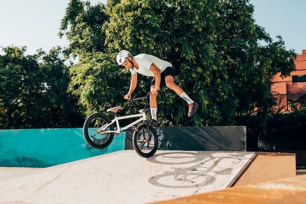 Молодой человек делает трюки с велосипедом bmx