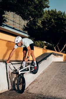 Тренировка молодого человека с велосипедом bmx