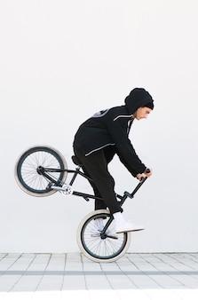 Гонщик делает фокус на белой стене. bmx райдер с велосипедом в полете на белом