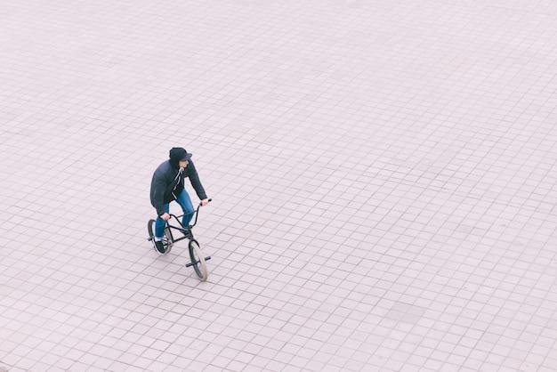 Минималистская фотография подростка на велосипеде bmx. вид сверху.