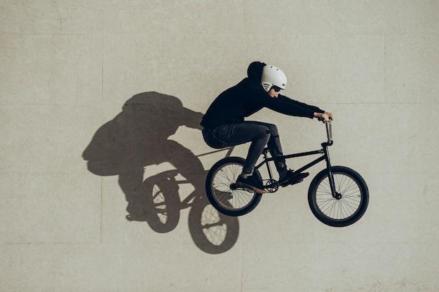 石の壁に投影された影でバニーホップを行うbmxer