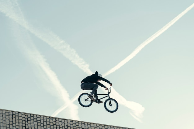 Bmxer doing a bunny hop on top a skate park with x form lines in the sky