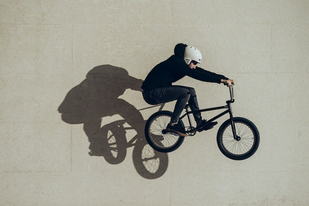 Bmxer doing a bunny hop with his shadow projected in a stone wall