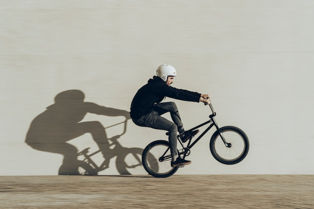 Bmxer doing a wheelie with his shadow projected in a stone wall