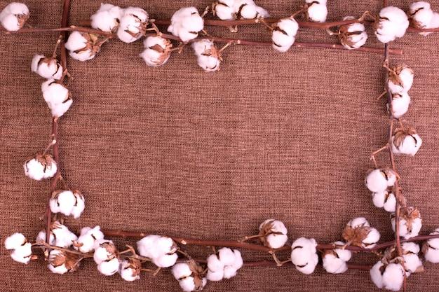 粗い茶色の黄麻布の上にふわふわの乾燥綿boが付いた花。