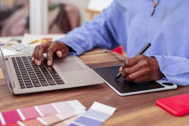 보드와 노트북. 작은 스마트 보드와 노트북을 사용하여 파란색 스웨터를 입고 패션 디자이너를 닫습니다