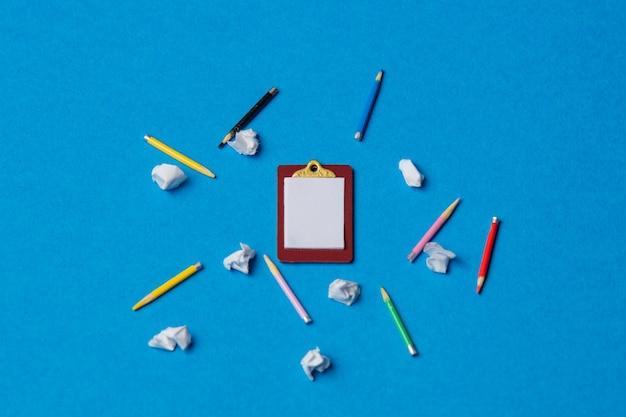 파란색 배경에 구겨진 종이가 있는 보드와 연필