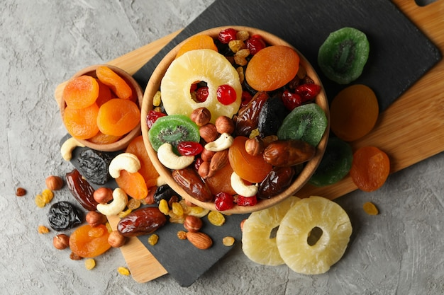 Board and bowls with dried fruits and nuts on gray