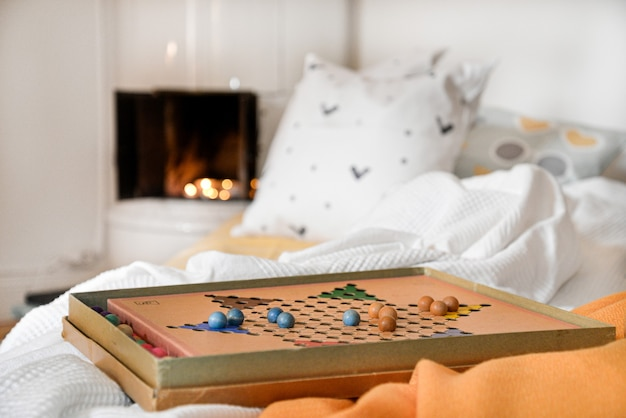 Board game on a bed with pillows on a blurred background
