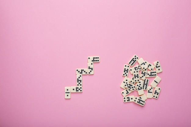 Board game dominoes on pink
