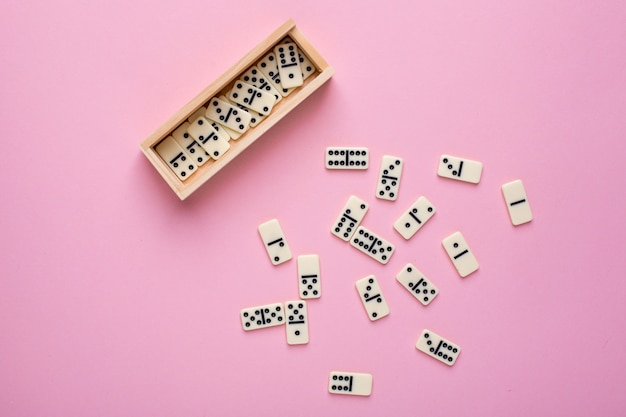Board game of dominoes on pink