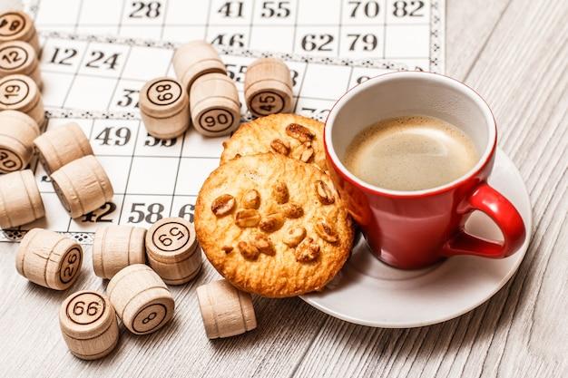 白い机の上にボードゲームの宝くじ。プレートにコーヒーとクッキーのカップが付いているロトのゲームのための木製のロトバレルとゲームカード