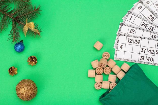 ボードゲーム宝くじ。宝くじ、クリスマスのモミの木の枝と緑の背景の上の円錐形のゲームのためのバッグとゲームカードと木製の宝くじの樽。上面図