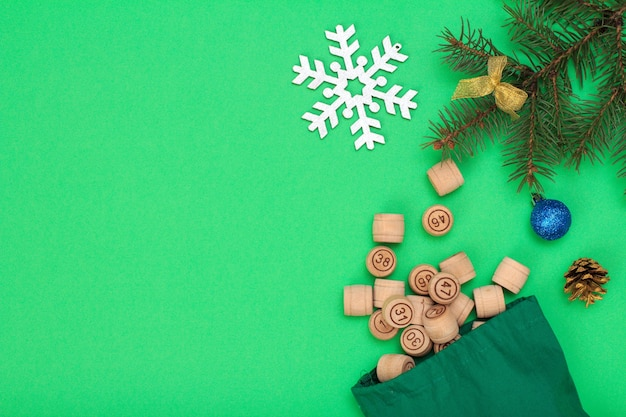 ボードゲーム宝くじ。宝くじ、クリスマスのモミの木の枝と緑の背景の上の円錐形のゲームのためのバッグと木製の宝くじの樽。上面図