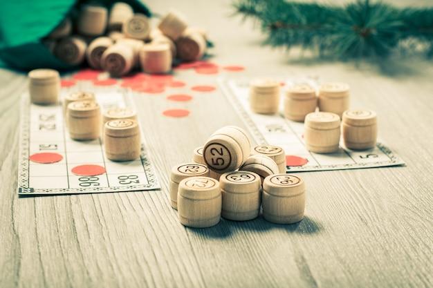 ボードゲーム宝くじ。緑のバッグ、ゲームカード、クリスマスのモミの木の枝が付いている木製の宝くじの樽。色調効果。