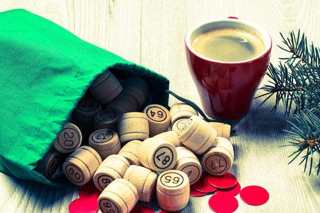 ボードゲーム宝くじ。緑のバッグ、ゲームカード、赤いチップと一杯のコーヒー、クリスマスのモミの木の枝が付いている木製の宝くじの樽。色調効果。
