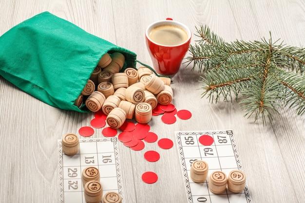 ボードゲーム宝くじ。緑のバッグ、ゲームカード、赤いチップとコーヒーのカップ、背景にクリスマスのモミの木の枝と木製の宝くじの樽