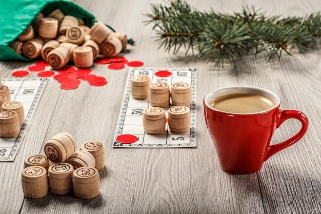 ボードゲーム宝くじ。緑のバッグ、ゲームカード、赤いチップと一杯のコーヒー、クリスマスのモミの木の枝が付いている木製の宝くじの樽。