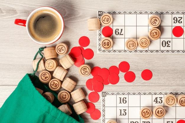 ボードゲーム宝くじ。緑のバッグ、ゲームカード、レッドチップ、コーヒー1杯が入った木製の宝くじ樽。上面図