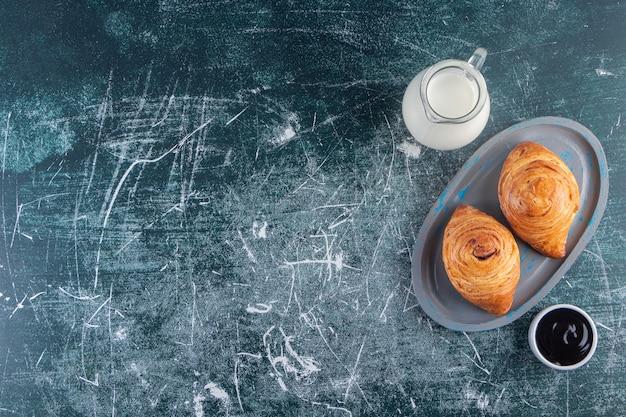 Un tagliere di rotoli di pasta sfoglia con una caraffa in vetro di latte fresco.