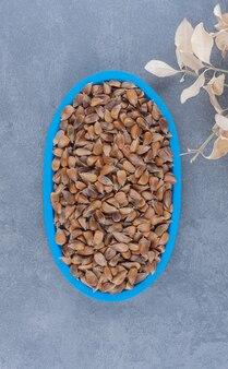 Una tavola di semi accanto alle foglie, sullo sfondo di marmo.