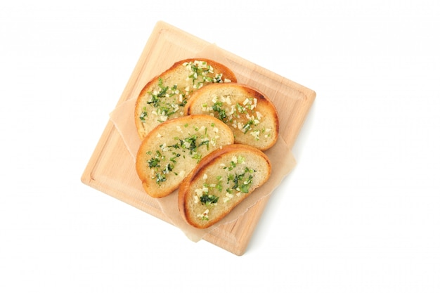 Board of toasted bread slices with garlic isolated on white