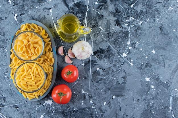 Una tavola di due tipi di maccheroni crudi con verdure e olio su uno sfondo di marmo.