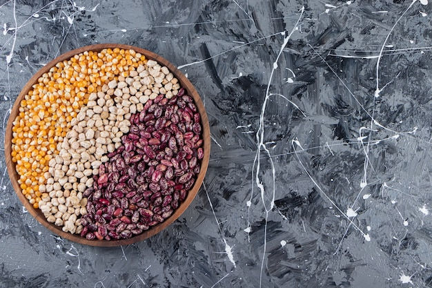 Un bordo di vari cereali, granaglie, semi, semole, legumi e fagioli.