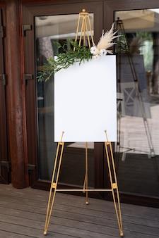 Доска, стоящая на траве со свадебной надписью. мокап для приглашения