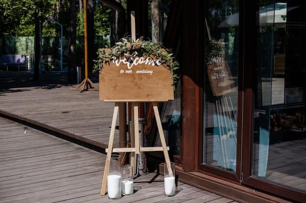 Доска, стоящая на траве со свадебной надписью welcome mockup для объявления