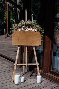 Доска, стоящая на траве со свадебной надписью welcome mockup