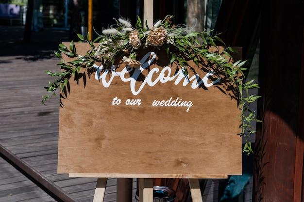 Доска, стоящая на траве со свадебной надписью добро пожаловать на наш свадебный мокап