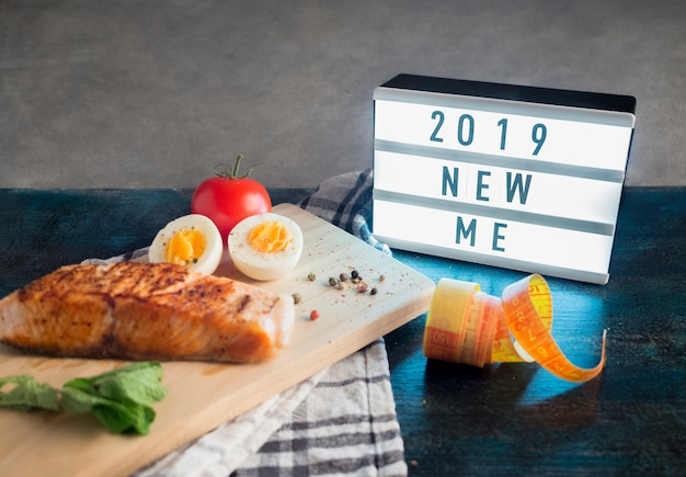 Board with 2019 new me inscription with roasted salmon on table