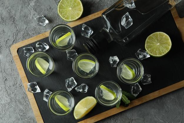 Доска с бутылкой и рюмками напитка с лаймом на серой стене