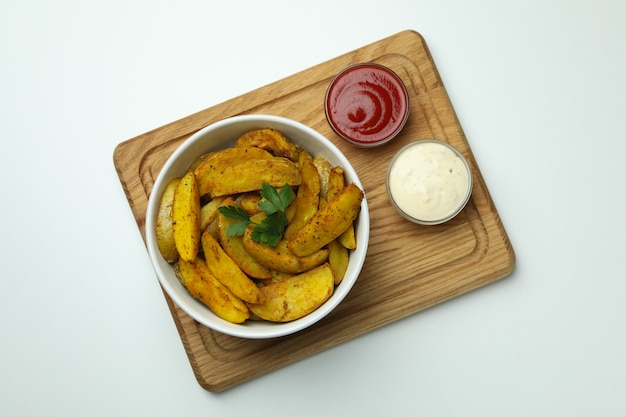 Board with bowl of potato wedges and sauces on white