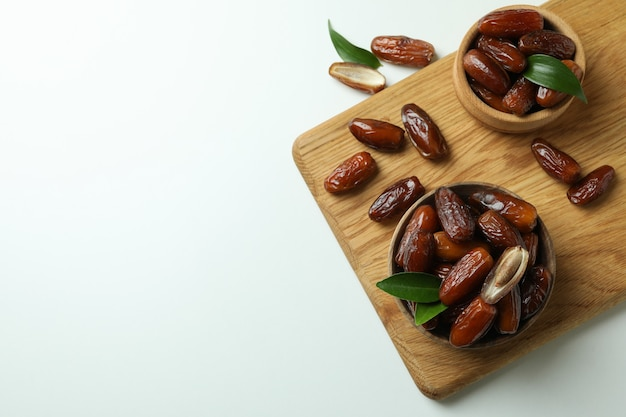 Board with bowls of dried dates on white