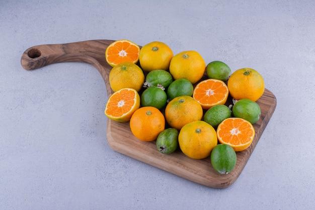 Bordo con un mazzo di mandarini e feijoas su fondo di marmo. foto di alta qualità