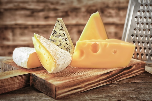 木製の背景にチーズとおろし金でボード