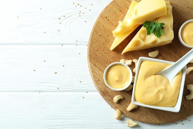 白い木製のテーブルにチーズソースと材料を乗せてボード