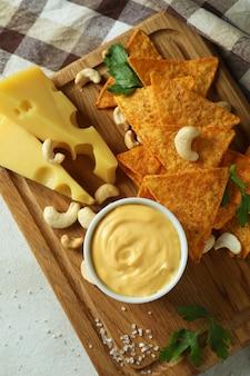 白い織り目加工のテーブルにチーズソースと軽食を乗せて