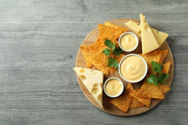 グレーのテクスチャードテーブルにチーズソース、チップス、チーズ、パセリを乗せたボード