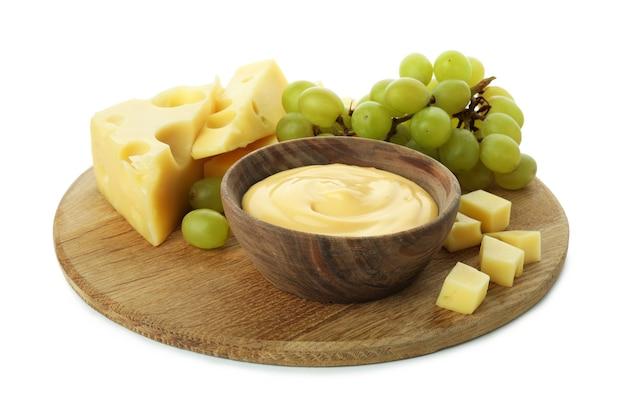 白い背景で隔離のチーズソース、ブドウ、チーズとボード