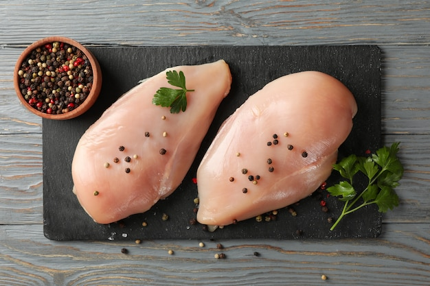 Board with chicken meat on wooden space. cooking chicken