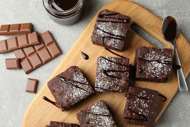 Доска с кусочками шоколадного торта и шоколад на сером, вид сверху