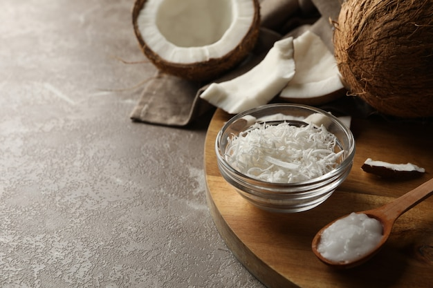 Board with coconut and coconut flakes on gray table