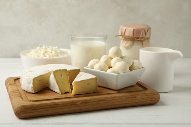 Доска с различными молочными продуктами на деревянных фоне
