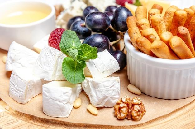 Доска с разными видами сыра. набор сырной смеси дор блю чедр, пармезан, бри, мед, соус, пальчиковый хлеб и виноград на деревянном поддоне. тарелка завтрака меню ресторана. ассортимент полезных закусок.