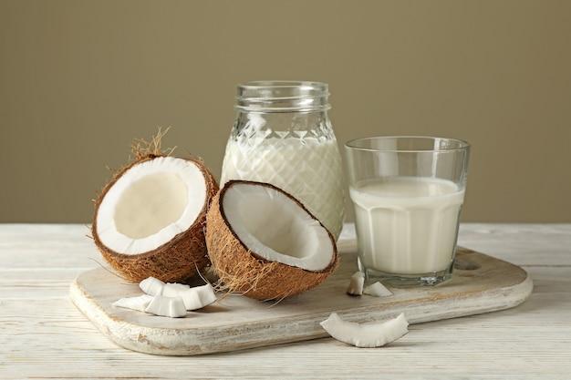 木製の背景に新鮮なココナッツとココナッツミルクでボード