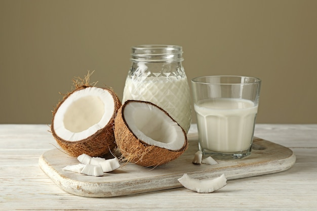 Board with fresh coconut and coconut milk on wooden background